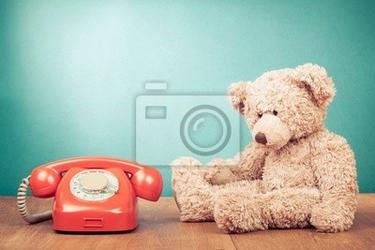 Obraz retro czerwony telefon i teddy bear w pobliżu mięty zielonej ściany
