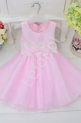 Różowa sukienka dla dziewczynki zdobiona w pasie białą koronką