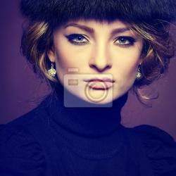 Obraz portret piękne blondynka w futrzanej czapce na brązowym