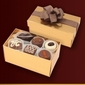 Czekoladki praliny w średnim złotym kuferku.