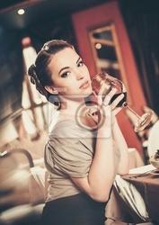 Obraz piękna młoda dziewczyna z kieliszkiem czerwonego winein restauracji