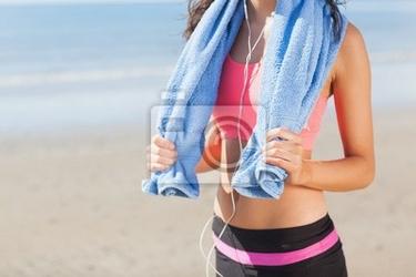 Obraz połowy sekcji zdrowej kobiety z ręcznikiem na szyi na plaży