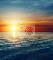 Fototapeta czerwony zachód słońca nad ciemną wodą