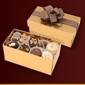 Czekoladki praliny w dużym złotym kuferku.