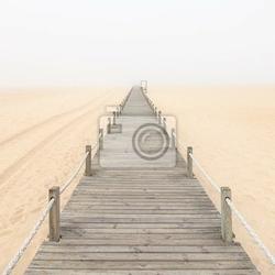 Fototapeta drewniana kładka w mglisty tle piasku plaży. portugalia.