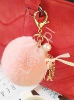 Breloczek do torebki, jasno różowy pompon z łańcuszkiem ozdobiony charmsem wieżą eiffla, chwostem i koralikiem