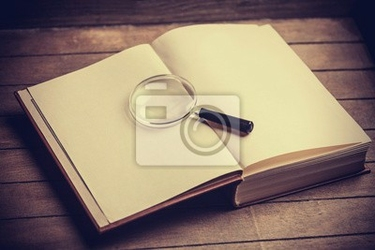 Obraz loupa i książka na drewnianym stole
